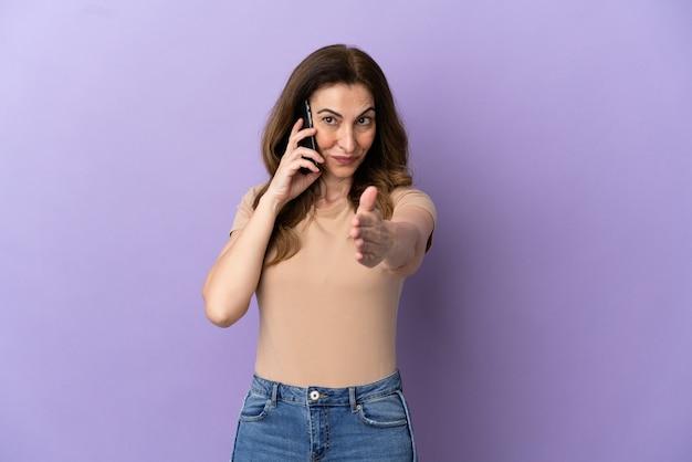 Donna caucasica di mezza età che utilizza il telefono cellulare isolato su sfondo viola che stringe la mano per chiudere un buon affare