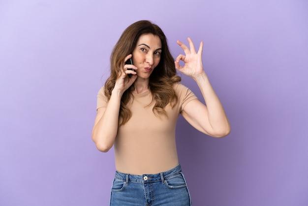 Donna caucasica di mezza età che utilizza il telefono cellulare isolato su sfondo viola che mostra segno ok con le dita