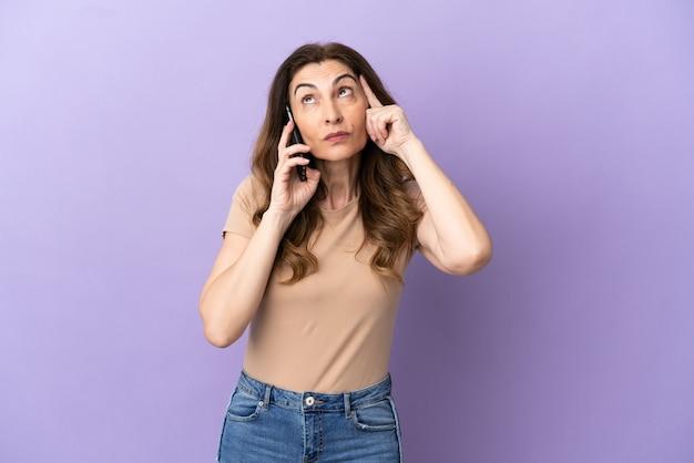 Donna caucasica di mezza età che utilizza il telefono cellulare isolato su sfondo viola pensando a un'idea