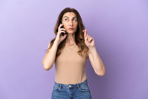 Donna caucasica di mezza età che utilizza il telefono cellulare isolato su sfondo viola con le dita incrociate e augurando il meglio