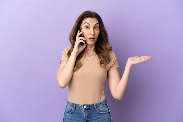 Donna caucasica di mezza età che utilizza il telefono cellulare isolato su sfondo viola con espressione facciale scioccata