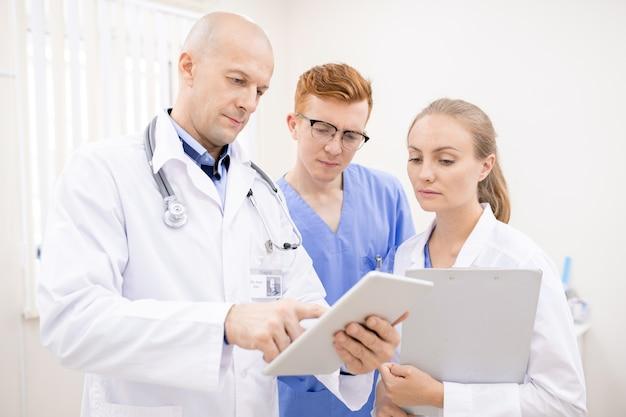 Medico di mezza età con touchpad che fa la presentazione a due giovani stagisti in cliniche contemporanee