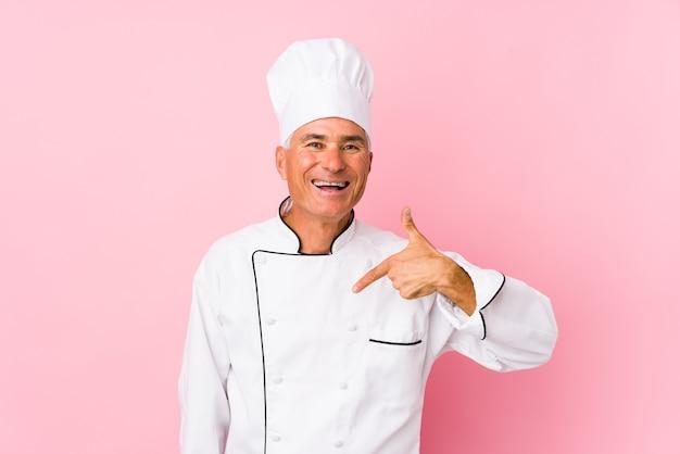 Persona isolata uomo di mezza età cuoco che punta a mano uno spazio di copia della camicia, orgoglioso e fiducioso