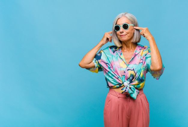 Donna fredda di mezza età che si sente confusa o dubita, concentrandosi su un'idea, pensando intensamente, cercando di copiare lo spazio sul lato