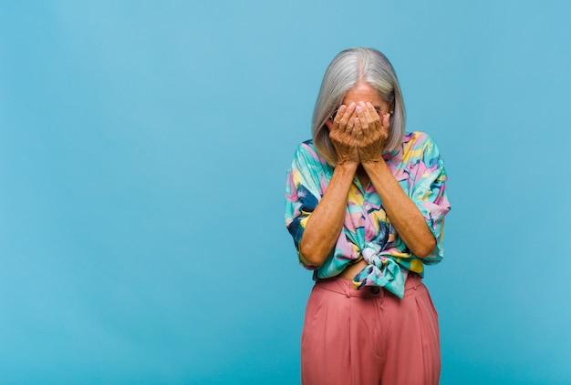 Donna fredda di mezza età che si sente triste, frustrata, nervosa e depressa, coprendosi il viso con entrambe le mani, piangendo