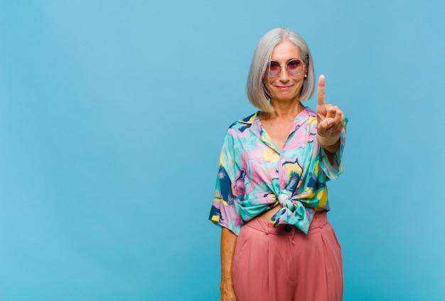 Donna fredda di mezza età che sorride e sembra amichevole, mostrando il numero uno o il primo con la mano in avanti, contando alla rovescia