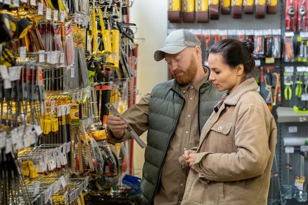 Coppia di mezza età che sceglie utensili manuali in un grande supermercato hardware