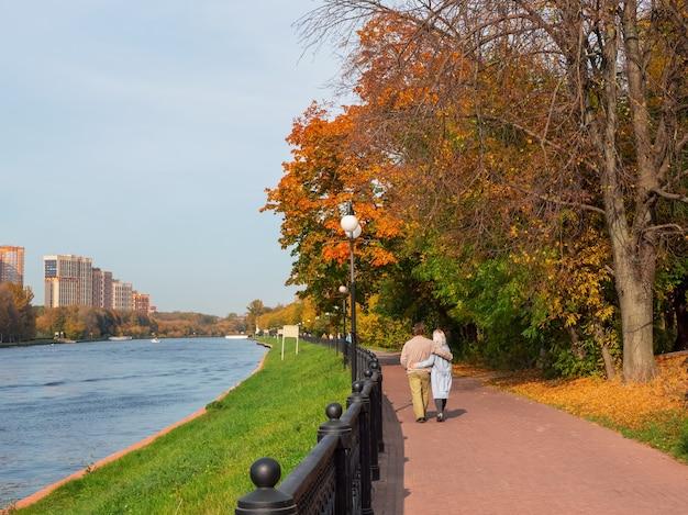 Una coppia di mezza età innamorata cammina abbracciata lungo l'argine autunnale.