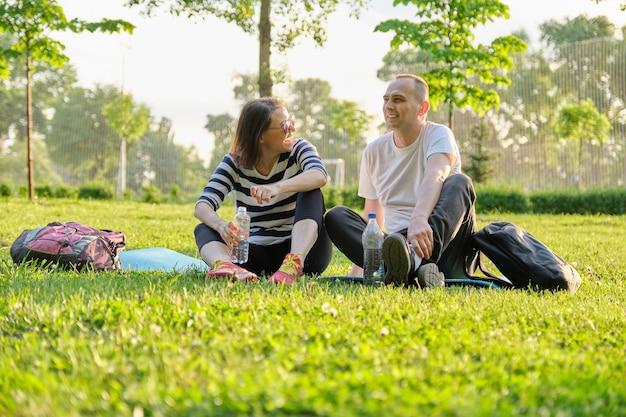 Coppia di mezza età che si siede sulla stuoia di yoga, uomo e donna che parlano acqua potabile rilassante. stile di vita sano attivo, relazione, sport, fitness nelle persone mature