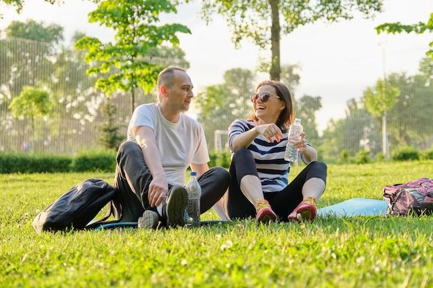 Coppia di mezza età che si siede sulla stuoia di yoga, uomo e donna che parlano acqua potabile rilassante. stile di vita sano attivo, relazione, sport, fitness nelle persone mature mature