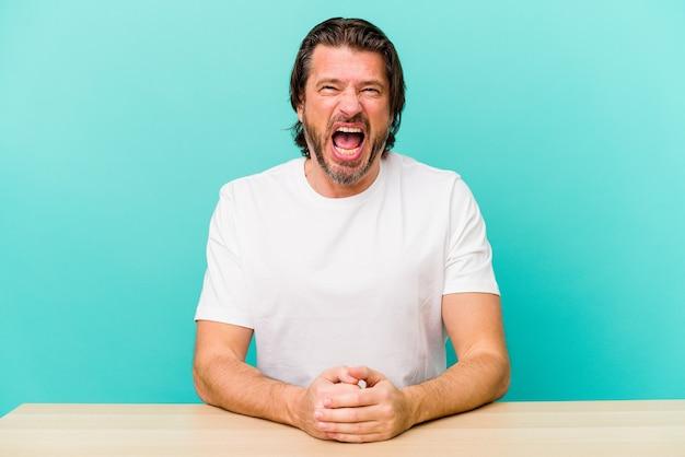 Uomo olandese invecchiato centrale che si siede isolato sulla parete blu che grida molto arrabbiato e aggressivo