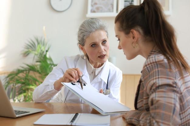 Terapista medico femminile di mezza età in consultazione con il paziente in ufficio.