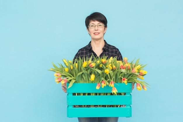 Fiorista femminile di mezza età che tiene scatola di legno blu dei tulipani sull'azzurro