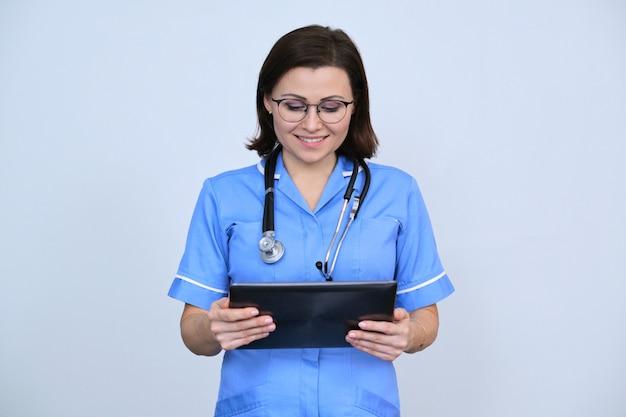 Operaio medico femminile di mezza età con tavoletta digitale