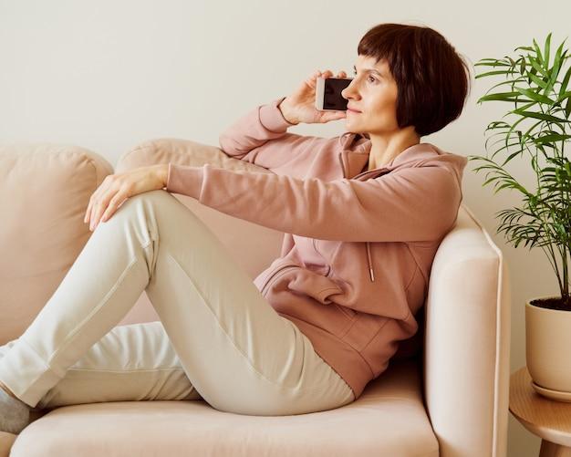 Donna di mezza età in abiti sportivi da casa pastello seduto sul divano e parlando con gli amici