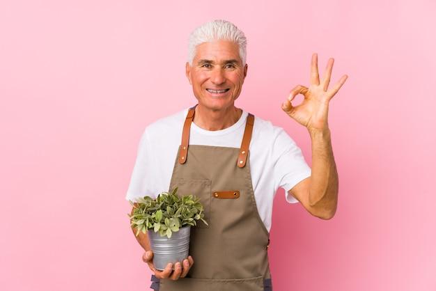 L'uomo di mezza età giardiniere isolato allegro e fiducioso che mostra gesto giusto.