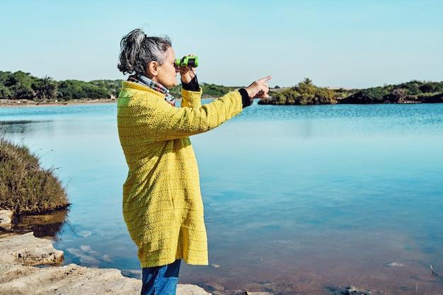 Donna bruna dai capelli grigi di mezza età in giacca gialla guarda gli uccelli in un lago con il binocolo e punta con il dito