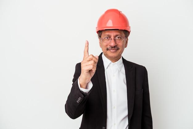 Uomo indiano di mezza età architetto isolato su sfondo bianco che mostra il numero uno con il dito.