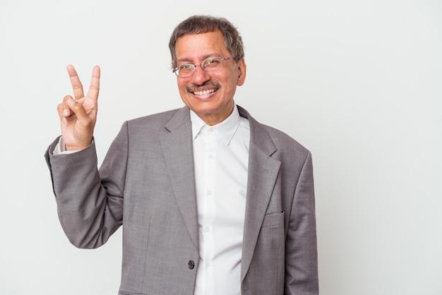 Uomo d'affari indiano di mezza età isolato su sfondo bianco gioioso e spensierato che mostra un simbolo di pace con le dita.