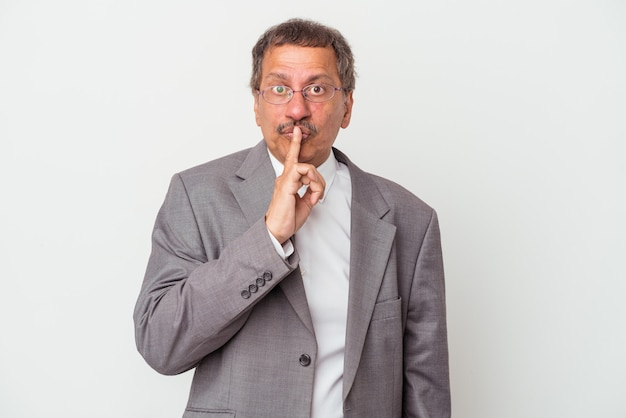 Uomo d'affari indiano di mezza età isolato su sfondo bianco mantenendo un segreto o chiedendo silenzio.