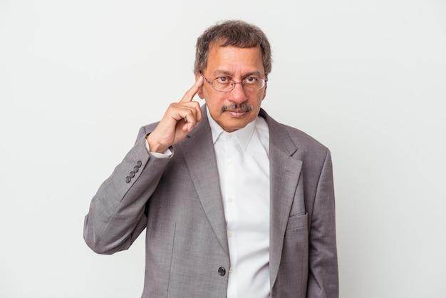 Uomo d'affari indiano di mezza età isolato su sfondo bianco che indica tempio con il dito, pensando, concentrato su un compito.
