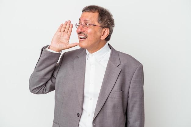 Uomo d'affari indiano di mezza età isolato su sfondo bianco che grida e tiene il palmo vicino alla bocca aperta.