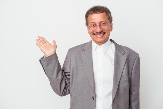 Uomo d'affari indiano di mezza età isolato su sfondo bianco che mostra uno spazio di copia su un palmo e tiene un'altra mano sulla vita.