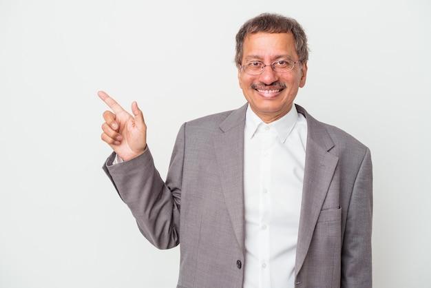 Uomo d'affari indiano di mezza età isolato su sfondo bianco sorridente e rivolto da parte, mostrando qualcosa in uno spazio vuoto.