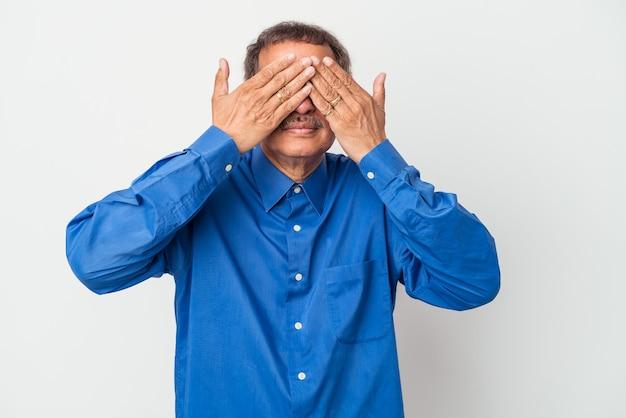 Uomo indiano di mezza età isolato su sfondo bianco impaurito che copre gli occhi con le mani.