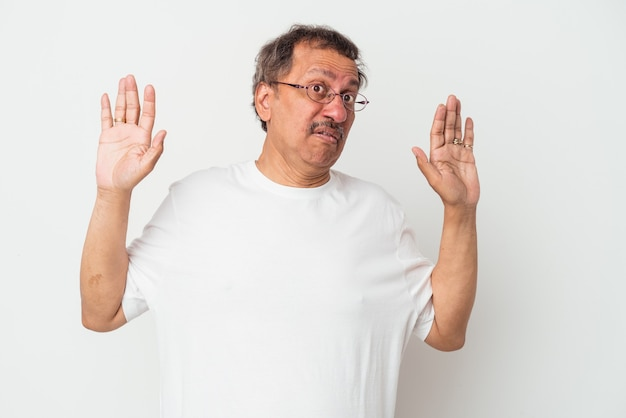 Uomo indiano di mezza età isolato su sfondo bianco scioccato a causa di un pericolo imminente