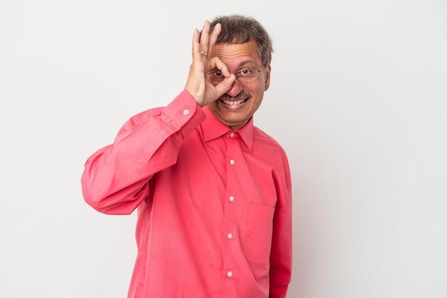 Uomo indiano di mezza età isolato su sfondo bianco eccitato mantenendo il gesto ok sull'occhio.