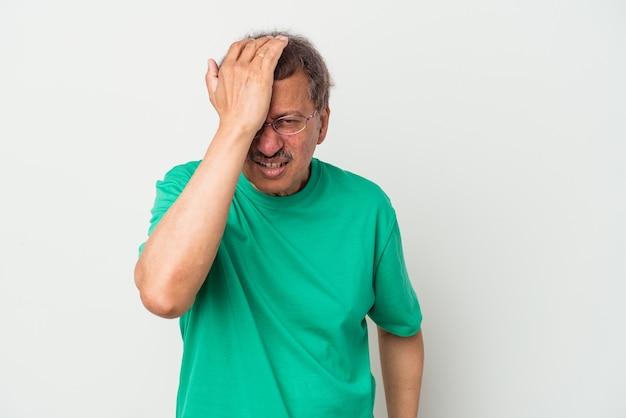 Uomo indiano di mezza età isolato su sfondo bianco dimenticando qualcosa, schiaffeggiando la fronte con il palmo e chiudendo gli occhi.