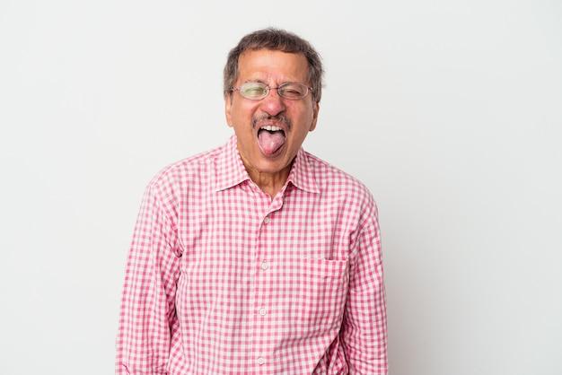 Uomo indiano di mezza età isolato su sfondo bianco divertente e amichevole che attacca fuori la lingua.