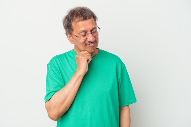 Uomo indiano di mezza età isolato su sfondo bianco guardando lateralmente con espressione dubbiosa e scettica.
