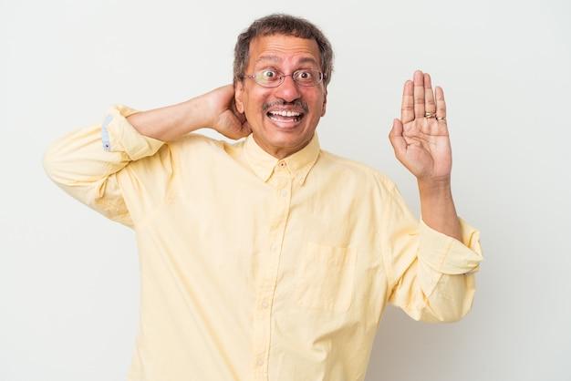 Uomo indiano di mezza età isolato su sfondo bianco che urla di rabbia.