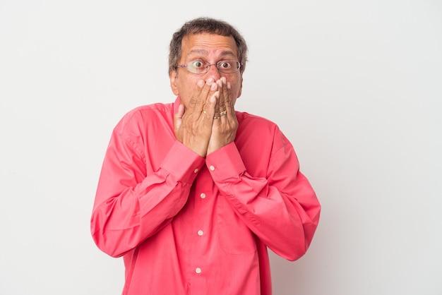 Uomo indiano di mezza età isolato su sfondo bianco scioccato che copre la bocca con le mani.