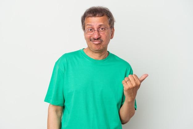 Uomo indiano di mezza età isolato su sfondo bianco scioccato indicando con il dito indice uno spazio di copia.