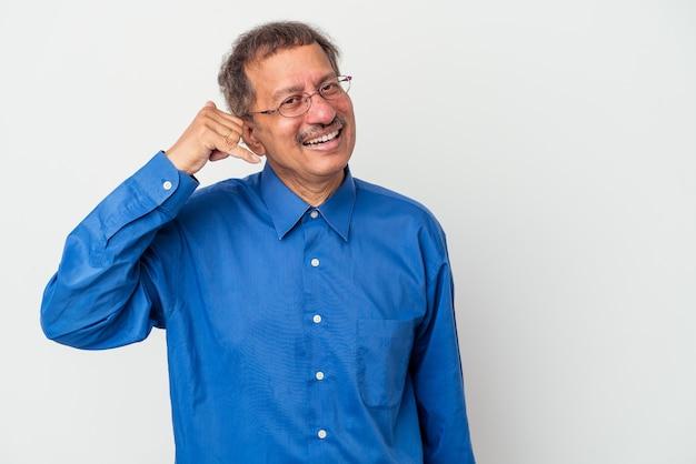 Uomo indiano di mezza età isolato su sfondo bianco che mostra un gesto di telefonata con le dita.