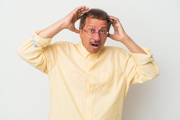 Uomo indiano di mezza età isolato su sfondo bianco sorpreso e scioccato.