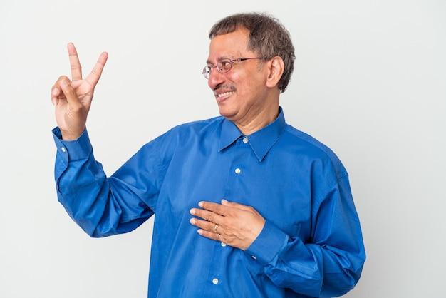 Uomo indiano di mezza età isolato su sfondo bianco prestando giuramento, mettendo la mano sul petto.