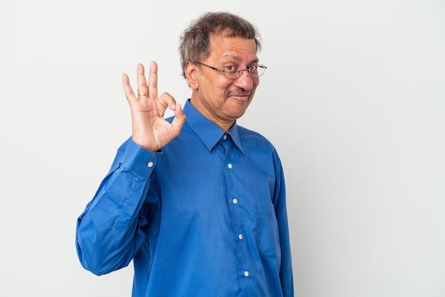 Uomo indiano di mezza età isolato su sfondo bianco strizza l'occhio e tiene un gesto ok con la mano.