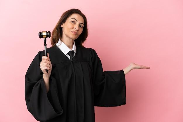 Donna giudice di mezza età isolata su sfondo rosa che estende le mani di lato per invitare a venire