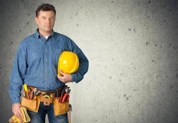 Costruttore maschio di mezza età su sfondo grigio muro