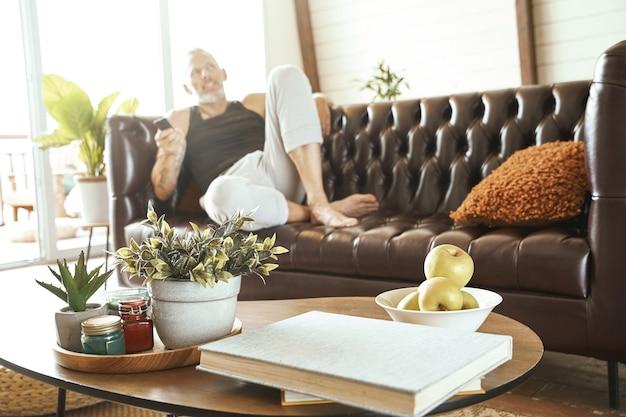 Uomo di mezza età in abiti casual con smartphone in mano che si rilassa su un comodo divano in