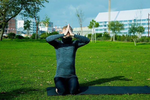 Uomo di mezza età che fa respirazione, rilassamento, yoga, stretching, esercizio fisico, allenamento nel parco utilizzando materassino yoga. posa di yoga naturale per principianti. concetto di assistenza sanitaria.