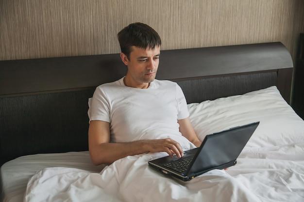 Un uomo di mezza età è seduto a letto nella sua camera da letto e lavora su un laptop. il concetto di lavoro a distanza