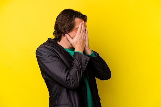 Uomo di mezza età isolato sul muro giallo paura che copre gli occhi con le mani