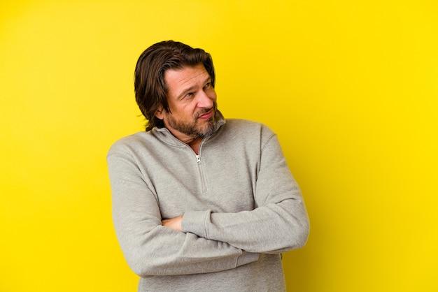 Uomo di mezza età isolato sulla parete gialla che sogna di raggiungere obiettivi e scopi