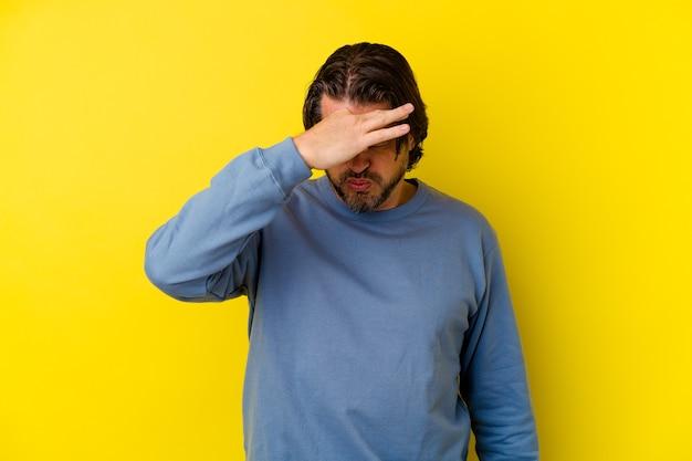 Uomo di mezza età isolato sul muro giallo con mal di testa, toccando la parte anteriore del viso