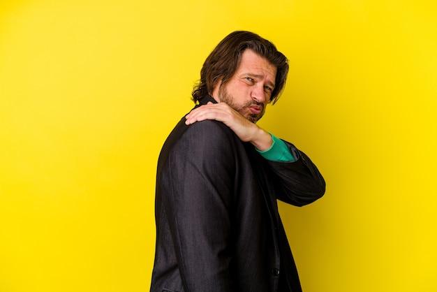 Uomo di mezza età isolato sulla parete gialla che ha un dolore alla spalla